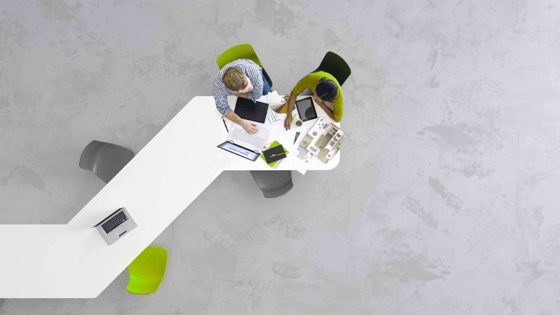 two_business_people_collaborating_at_desk_from_above