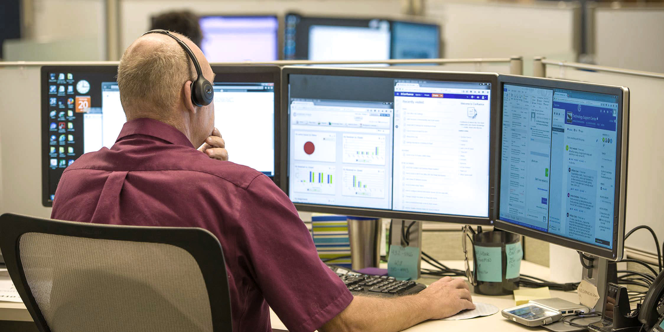 Tech support worker working at a desk with 3 monitors