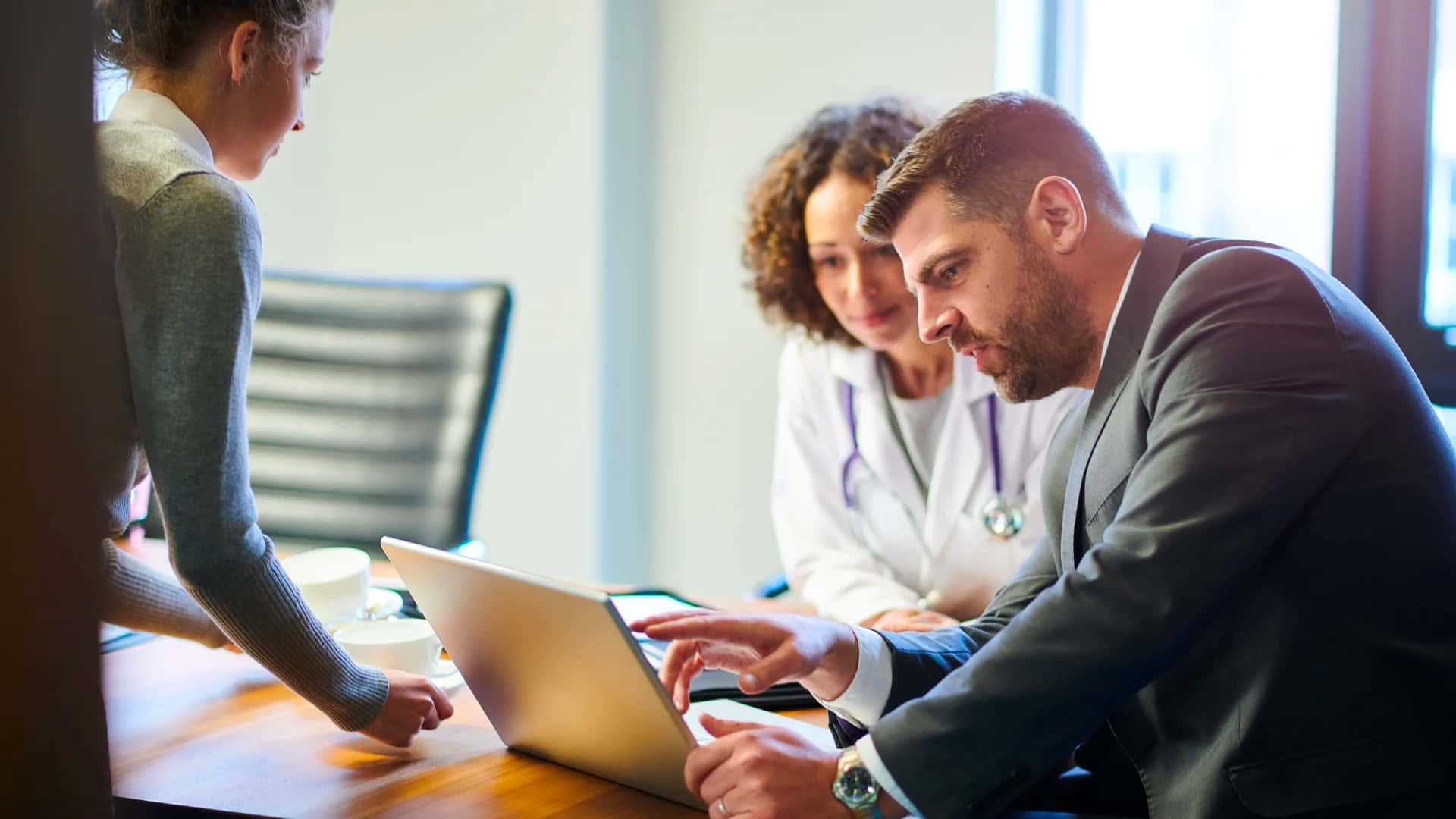 A person in a business suite reviewing IT files on a laptop with a person in a lab coat and stethoscope