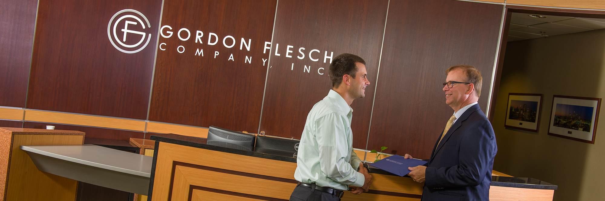two-men-talking-at-desk-in-front-of-gordon-flesch-sign.jpg