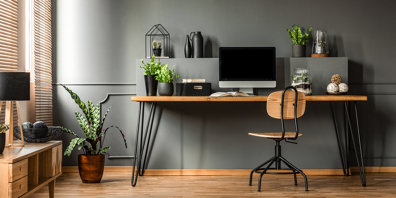 Desk with computer, plants, and other office items on a wooden floor with a wooden swivel chair.