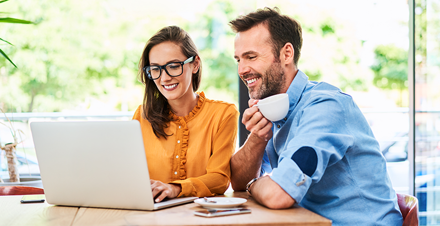 man and woman drinking coffee looking at computer