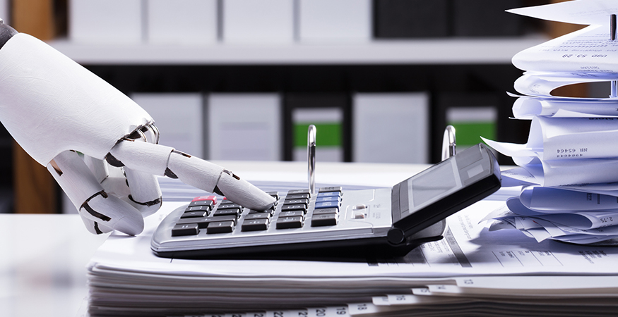 An humanoid robot hand typing on a large calculator.
