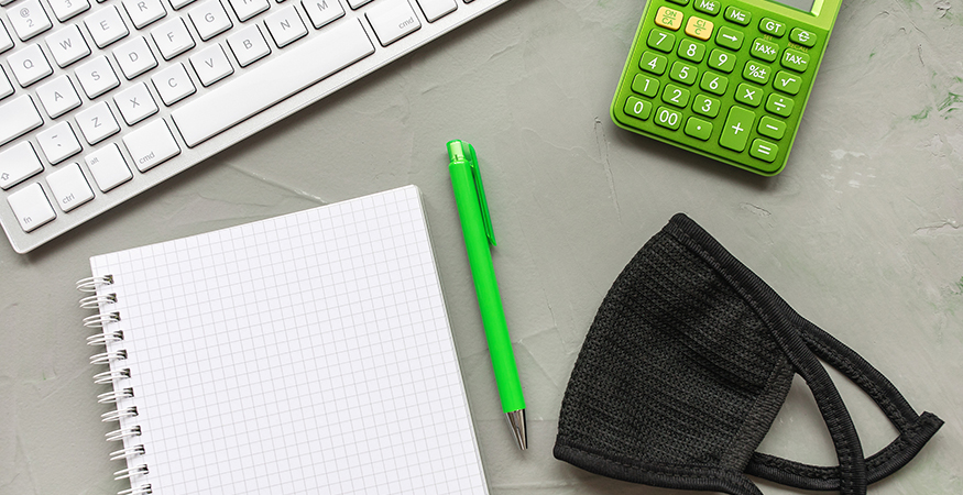 Desktop with a pen, keyboard, graph paper, calculator, and face mask.