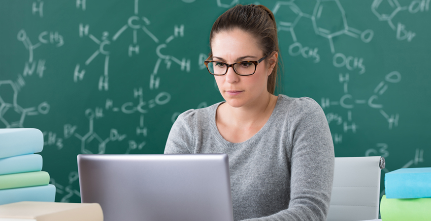 woman in science class looking at laptop