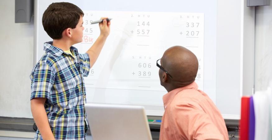 kid writing on whiteboard next to teacher